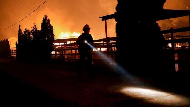 A firefighter runs along a dirt road during the wind-driven Kincade Fire in Windsor, California, October 27, 2019