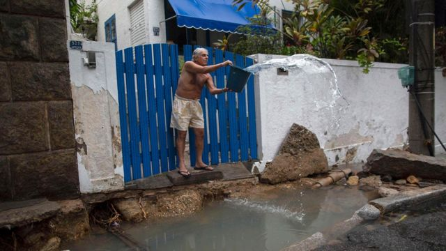 A man takes water out of the driveway of his home