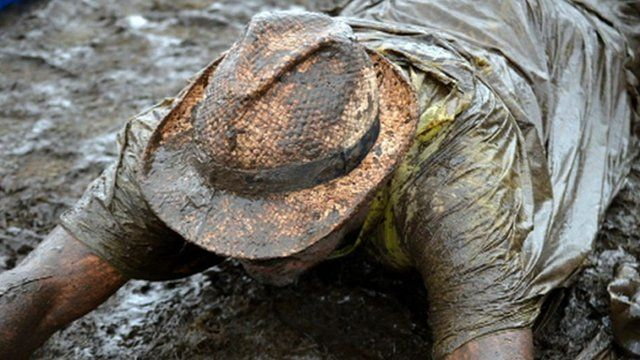 A music fan lies in the mud at the V Festival in Staffordshire