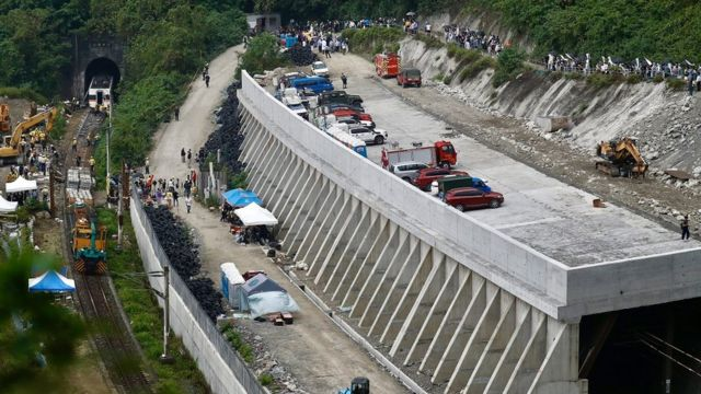 Relatives of victims grief as they pray near the site where a train derailed in a tunnel north of Hualien County, eastern Taiwan, 03 April 2021