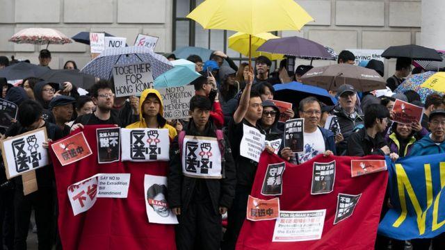 倫敦的示威者舉起象徵2014年雨傘運動的黃色雨傘。