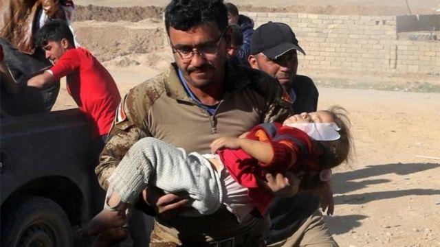 أب يحمل طفلته الجريحة
