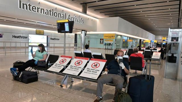 Passengers sit socially distanced in the arrivals hall in Heathrow Airport