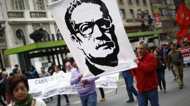 Manifestantes sostienen un cartel con el rostro de Salvador Allende