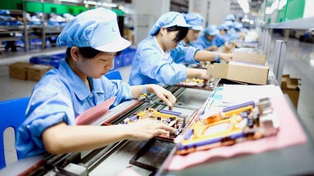 Trabalhadores em uma linha de montagem de uma fábrica de laptops em Shenzhen, na China