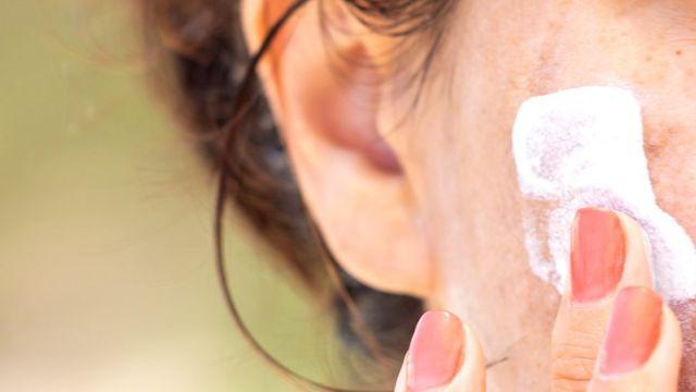 Mujer aplicando crema en una mejilla.