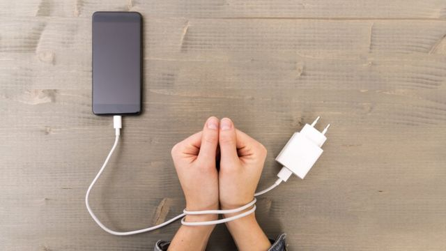 Foto de una manos amarradas al cable de un teléfono.