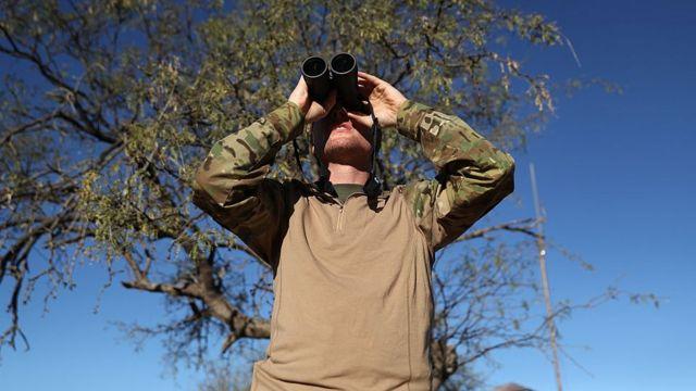 Paramilitar observa fronteira com México no Arizona com binóculo