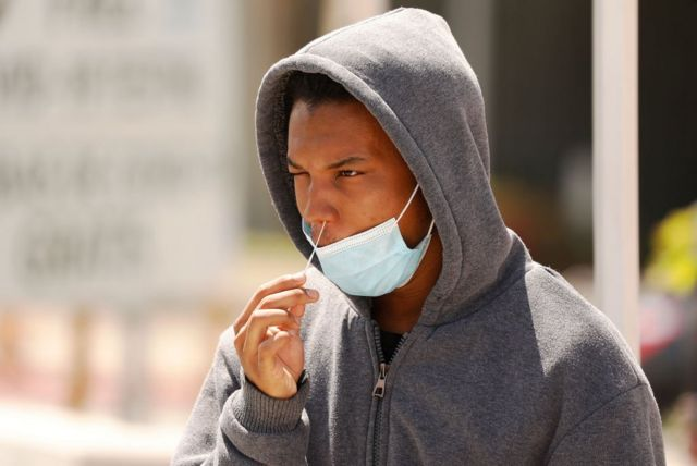 A young man in a hoodie adminsters a swab test on himself