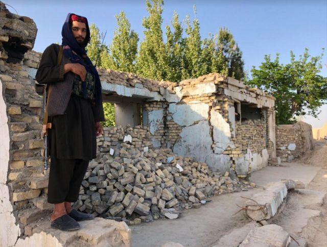 আমেরিকান বোমায় বিধ্বস্ত এক মসজিদের বাইরে একজন তালেবান যোদ্ধা
