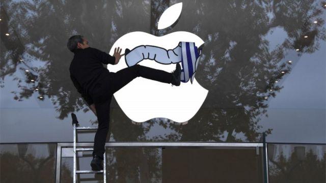 یک معترض به عملکرد اپل از نظر شفافیت مالی و همچنین پرداخت مالیات در فروشگاه اپل در جنوب فرانسه