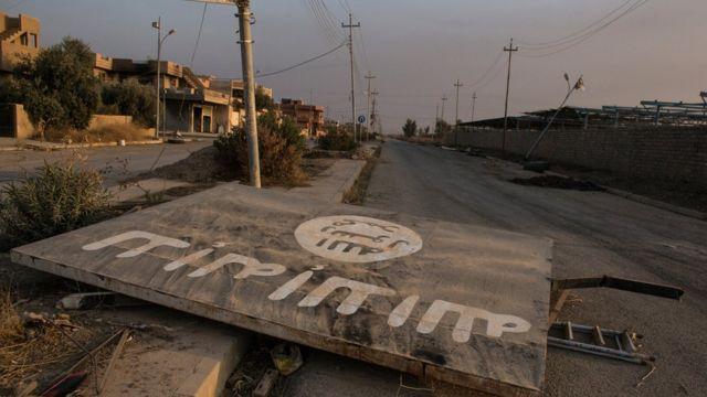 لافتة لتنطيم الدولة الاسلامية ساقطة على الارض في الموصل