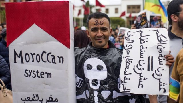 """A Moroccan protester holds a banner reading in Arabic """"20-year sentence = 20-years injustice"""""""