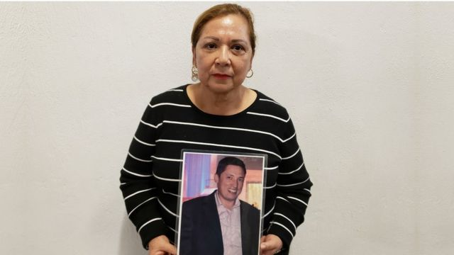 Guadalupe Aguilar holds up a framed photograph of her missing son