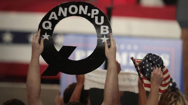 Una persona sostiene un cartel de Q