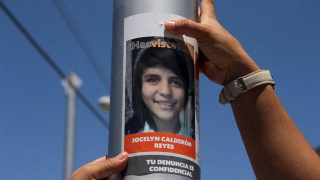 Una manos de mujer colocan un cartel en un poste pidiendo información sobre una mujer desaparecida en Ciudad Juárez