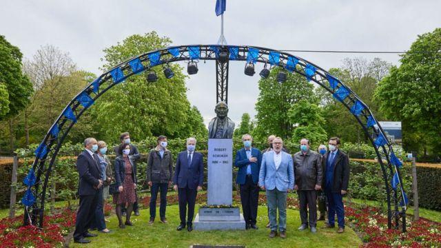 Funcionarios de la UE celebrando el Día de Europa en un busto de Robert Schuman