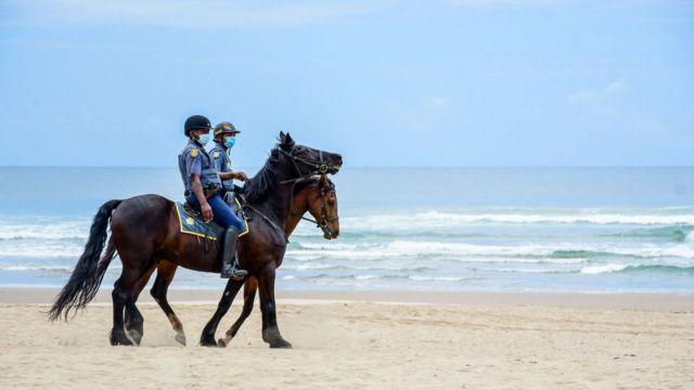 Policía en una playa en Sudáfrica.
