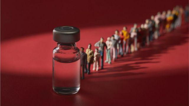 Frasco gigante de vacina com fila de pessoas na frente