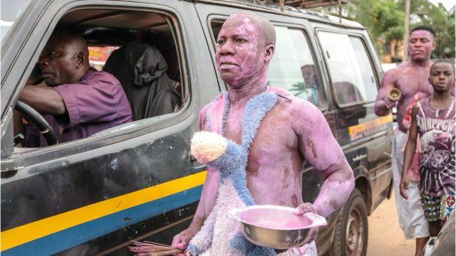 Mwanamume aliyepakwa rangi ya zambarawe akitembea karibu na gari kwenye mitaa ya mji wa Arondizuogu wakati wa tamasha la Ikeji Festival nchini Nigeria