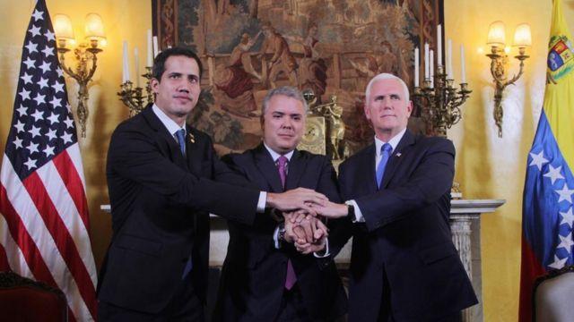 Juan Guaidó, autoproclamado presidente interino da Venezuela; Iván Duque Márquez, presidente da Colômbia; e Mike Pence, vice-presidente dos Estados Unidos apertam mãos no encontro do Grupo de Lima, em 25 de fevereiro de 2019