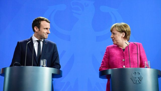 Macron and Merkel sharing a smile during a press conference