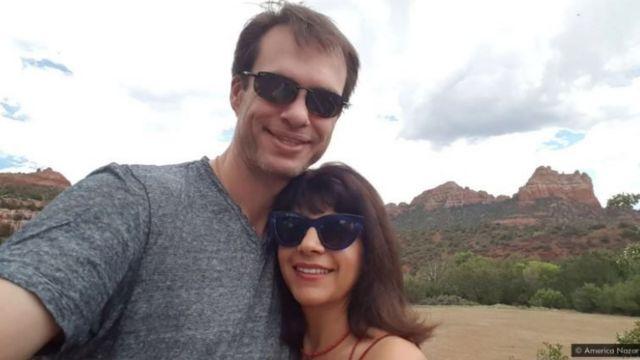 America e o marido abraçados e sorrindo para selfie, em paisagem natural
