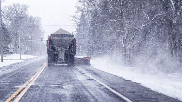 Camión lanzando sal en una calle congelada