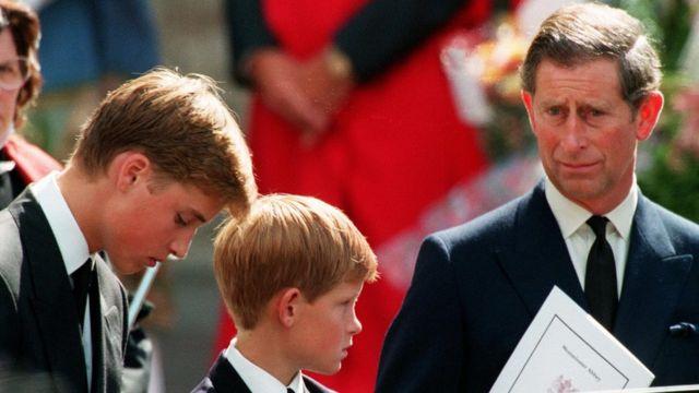 El príncipe William mira cabizbajo al suelo junto a su hermano Harry y su padre, el príncipe Carlos, el día del funeral de Diana de Gales