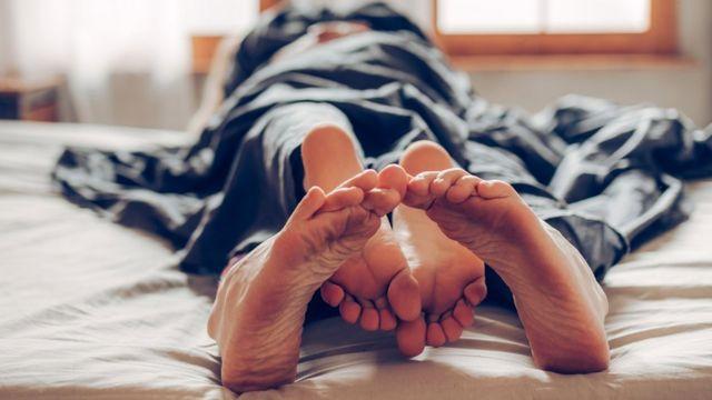 Pies entrelazados en una cama.