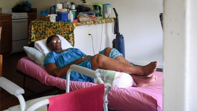 Mary Mitchell, 82, lays on a hospital bed in her room, without power, food or water at Cypress Run assisted living facility in Immokalee, Florida.