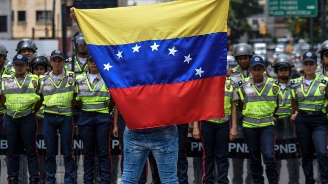Un manifestante con la bandera de Venezuela frente a la policía