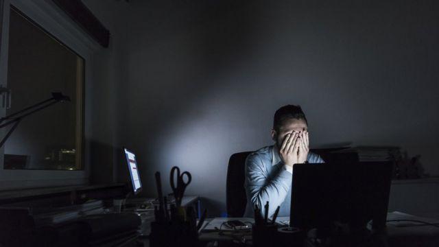 Wyczerpany biznesmen siedzi wieczorem przy biurku.