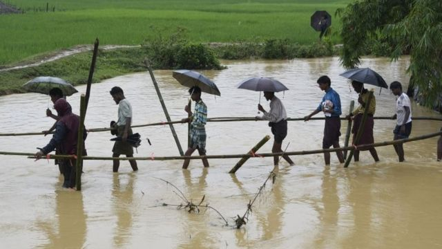 Rohingya Muslim refugees cross floodwater in Thyangkhali refugee camp near the Bangladesh town of Ukhia on 17 September 2017.