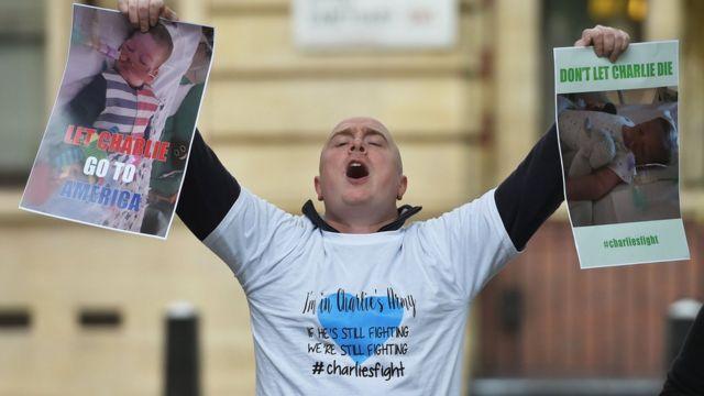 """Hombre protestando frente a los tribunales con carteles que dicen: """"Dejen a Charlie ir a Estados Unidos""""."""