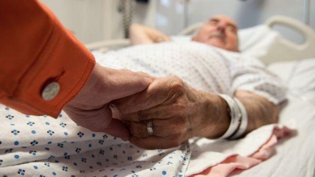 Hombre enfermo le toma la mano a su mujer.