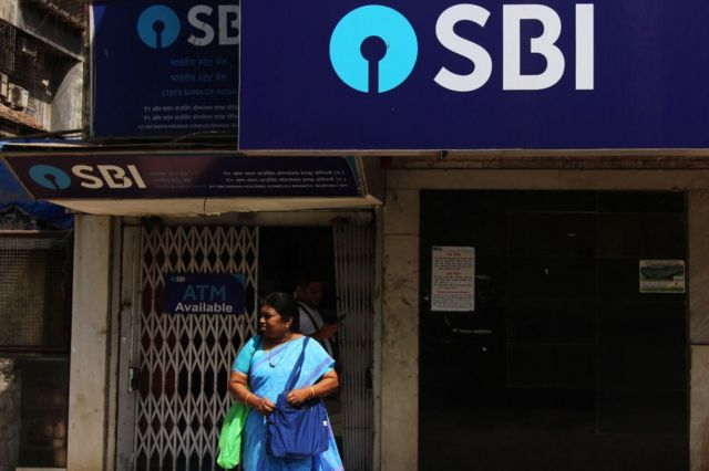 A woman stands in front of State Bank of India (SBI) bank branch in Mumbai, India on 29 March 2019.