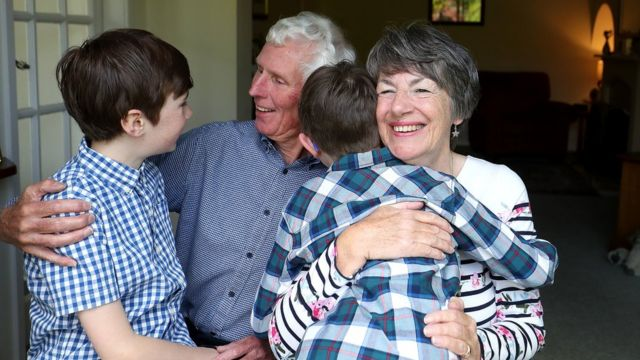 Sue and Alan Rickett hug their grandchildren Ben (left) and Isaac (right) for the first time in over a year, in anticipation of lockdown restrictions being eased in England.