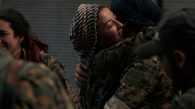 Syria Democratic Forces (SDF) female fighters embrace each other in the city of Manbij