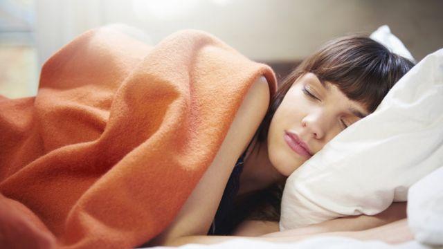 Mulher dormindo sob travesseiro com cobertor laranja