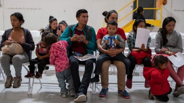 Migrants from Latin America wait to make phone calls to their family in friends who host them in the US, at a migrant centre in El Paso, Texas, April 2019