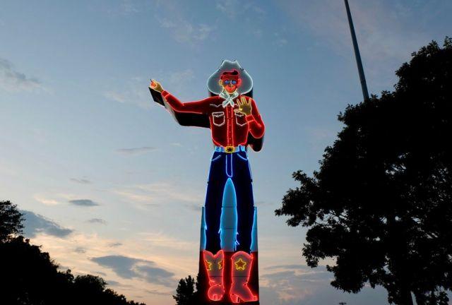 A neon sign of a cowboy