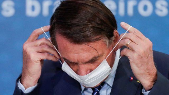Em frente a painel de evento, Bolsonaro coloca máscara no rosto
