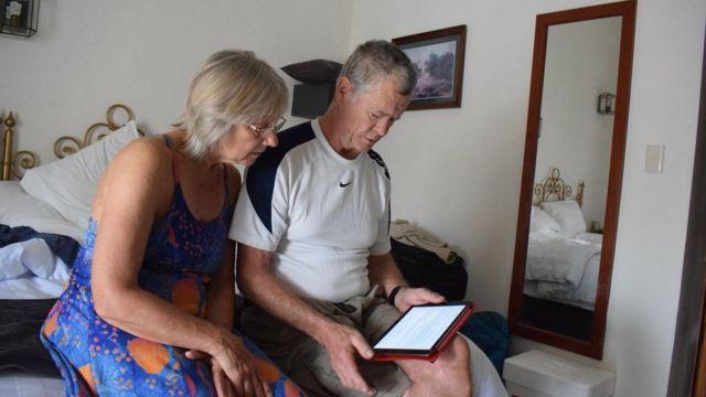 Dos turistas ven internet en su tablet.