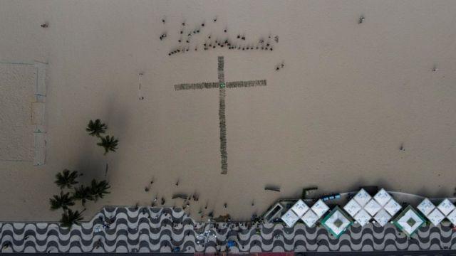 Foto áerea mostra cruz formada por rosas na areia da praia de Copacabana
