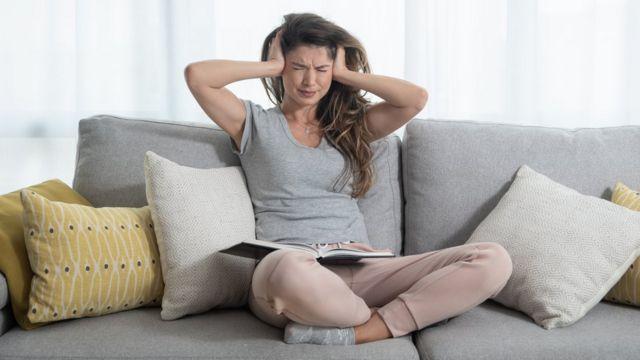 kadın eller kulaklarının üzerinde kanepede