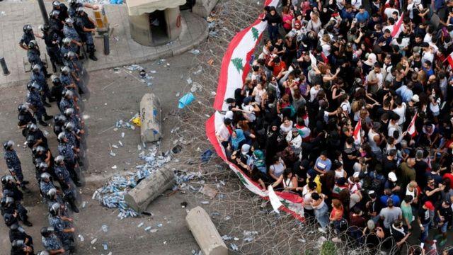 قوات من الشرطة اللبنانية والمتظاهرين تفصل بينهم أسلاك شائكة في بيروت.
