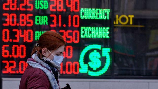 Mujer frente a una casa de cambio de monedas.