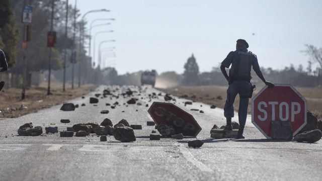 South African police forces stand at a barrier of stones made by protesters during an ongoing service delivery protest south of Johannesburg, South Africa - Saturday 23 July 2016