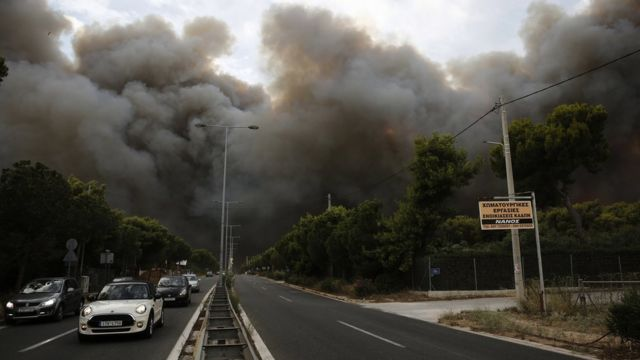 Smoke rise over an avenue during a forest fire in Neo Voutsa, a north-eastern suburb of Athens, Greece, 23 July 2018.